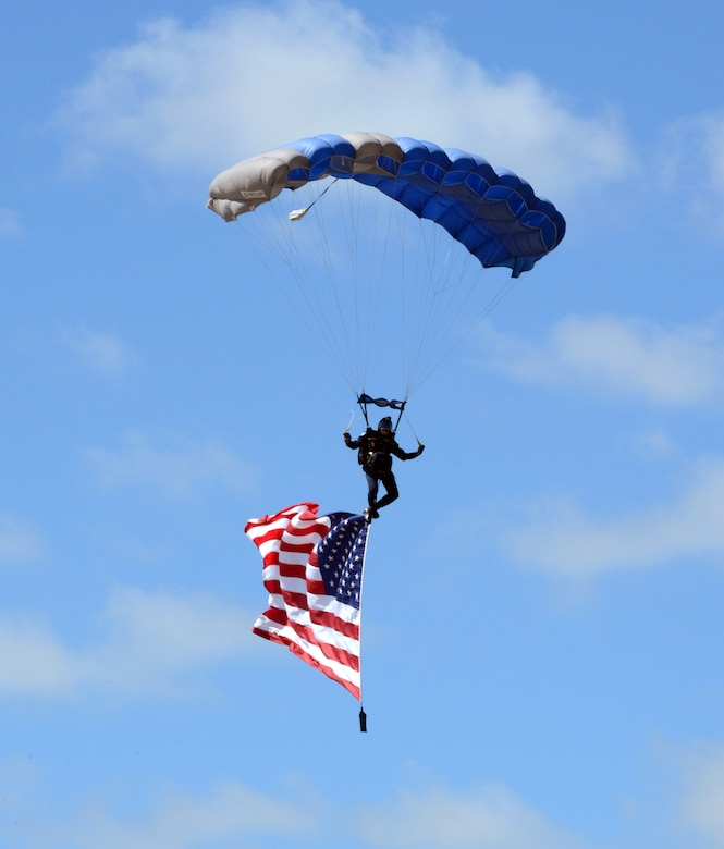 The Wings of Blue, a USAF Academy parachute team, captivated the audience with three members of the team demonstrating their precision parachute piloting skills before a fourth member gracefully glided down carrying the American Flag. (Air Force photo by Kelly White)