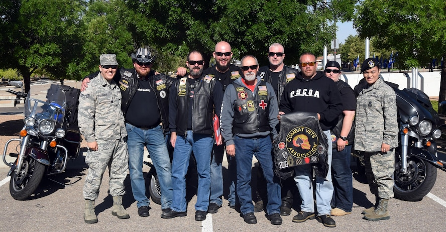 Members of the Combat Veterans Motorcycle Association pose with Team Kirtland airmen at the New Mexico Veterans Memorial, May 30, 2017. The veterans rode over to the New Mexico Veterans Memorial, where they had a chance to remember the fallen with Kirtland airmen and allow the airmen to sign flags that the group was carrying. (U.S. Air Force Photo/Joanne Perkins)