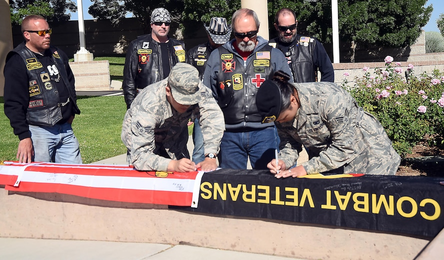 Senior Airman Chandler Baker, 377th Air Base Wing Public Affiars, and Senior Airman Karla Estrada, 377th Security Forces Squadron, sign flags at the New Mexico Veterans Memorial, May 30, 2017. The flags are being carried by members of the Combat Veterans Motorcycle Association. Two of the flags will go to each naval vessel the veterans stop at on their ride and the third will go to the association's board of directors during the association's annual conference. (U.S. Air Force Photo/Joanne Perkins)