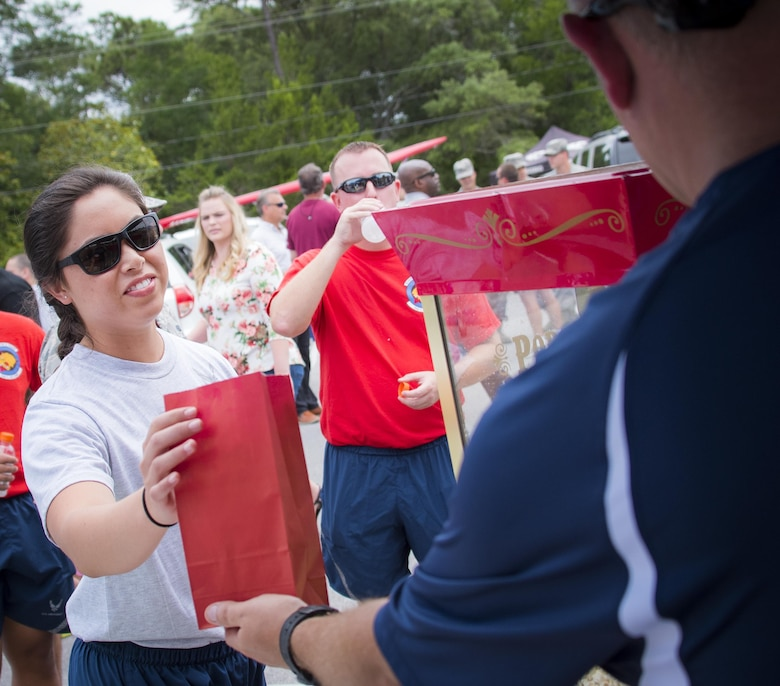 An Airman receives a bag of popcorn from a vendor during the Eglin Connects event at Eglin Air Force Base, Fla., June 2.  The event to help promote resiliency featured information booths, sporting events and a car show.  (U.S. Air Force photo/Samuel King Jr.)
