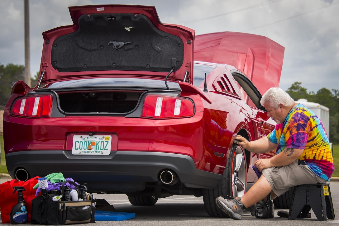 A Mustang owner ensures his tire are clean and shiny during the Eglin Connects event at Eglin Air Force Base, Fla., June 2.  The event to help promote resiliency featured information booths, sporting events and a car show.  (U.S. Air Force photo/Samuel King Jr.)