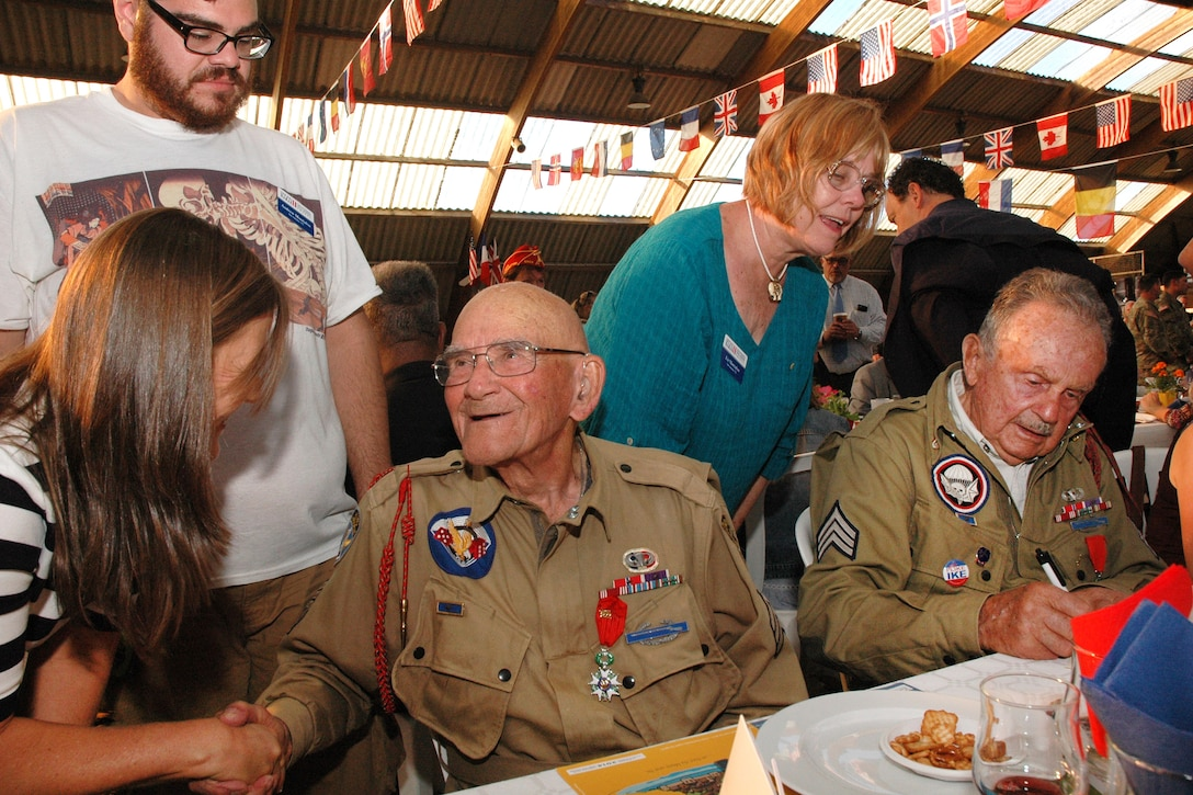 World War II veteran Bob Noody shakes hands with a well-wisher while Dan McBride signs an event program as citizens honor the veterans' role in the liberation of France during a dinner in Sainte-Mere-Elise, France