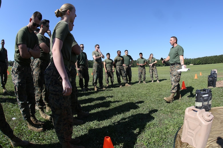 Gunnery Sgt. Anthony Stockman briefs a group of Marines assigned to Marine Aircraft Group 29, 2nd Marine Aircraft Wing, about the rules of the M-16A4 service rifle assembly and disassembly relay race at Marine Corps Air Station New River, N.C., May 26, 2017. The race included a low crawl to a rifle where one Marine would disassemble the rifle and crawl back. Then the next Marine would crawl and reassemble the weapon. Alongside the events, MAG-29 conducted classes and guided discussions to assist Marines with identifying and preparing to mitigate upcoming risk during the summer months. Stockman is the MAG-29 personnel support detachment first sergeant. (U.S. Marine Corps photo by Pfc. Skyler Pumphret/Released)