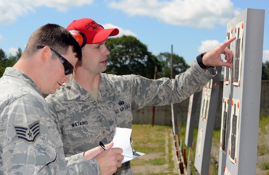 Staff Sgt. Daniel Watkins (right), 627th Security Forces Squadron combat arms instructor, shows Staff Sgt. Carl Kocon, 7th Airlift Squadron loadmasters, what areas of a target he hit, during the Elementary Level Rifle Excellence Competition May 31, 2017, at Joint Base Lewis-McChord, Wash. The competition was hosted by the 627th SFS combat arms section and is the second competition of its kind to be held at JBLM. (U. S. Air Force photo/Senior Airman Jacob Jimenez)