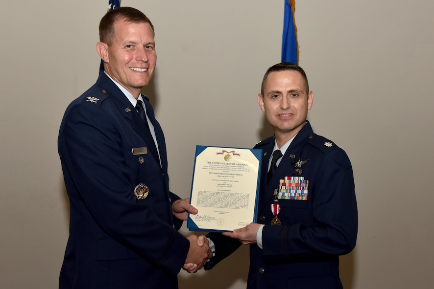 U.S. Air Force Col. Jeffery Sorrell, 17th Training Wing Vice Commander, presents a Meritorious Service certificate to Lt. Col. Edward Harris, 17th Comptroller Squadron Commander, during the 17th CPTS Change of Command ceremony at the Event Center on Goodfellow Air Force Base, Texas, June 2, 2017. The event honored Harris' service to his unit and welcomed its new commander Maj. Nelson Mitchell. (U.S. Air Force photo by Staff Sgt. Joshua Edwards/Released)