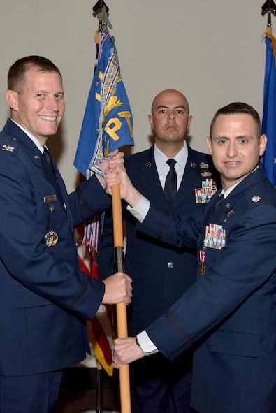 U.S. Air Force Lt. Col. Edward Harris, 17th Comptroller Squadron Commander, passes the unit guideon to Col. Jeffery Sorrell, 17th Training Wing Vice Commander, during the 17th CPTS Change of Command ceremony at the Event Center on Goodfellow Air Force Base, Texas, June 2, 2017. The event honored Harris' service to his unit and welcomed its new commander Maj. Nelson Mitchell. (U.S. Air Force photo by Staff Sgt. Joshua Edwards/Released)