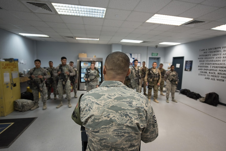 U.S. Air National Guard U.S. Air Force Master Sgt. Oscar Espinosa, 407th Expeditionary Security Forces flight chief, gives instructions to Airmen and U.S. Marines during a guardmount briefing May 10, 2017, in Southwest Asia. Espinosa, a guardsman with the 254th Security Forces Squadron from Andersen Air Force Base, deployed in support of Operation Inherent Resolve. As flight chief, Espinosa coordinates gate guard and patrol teams from both services and international coalition members. (U.S. Air Force photo by Staff Sgt. Alexander W. Riedel)