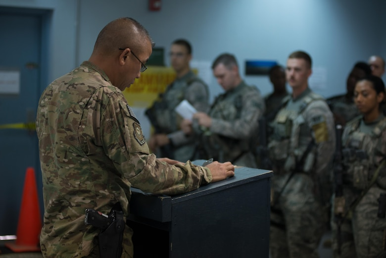 U.S. Air National Guard Master Sgt. Anthony Arriola, flight chief with the 407th Expeditionary Security Forces Squadron, left, briefs Airmen and U.S. Marines during guard changeover May 13, 2017, in Southwest Asia. Arriola works as part of the base defense operations center to oversee inegrated base defense activities, from patrols to vehicle search and gate guard sections. Arriola is deployed from the 254th Security  Forces Squadron of the Guam Air National Guard and serves as a civilian police officer with the Guam Police Department when not on active Air Force orders. (U.S. Air Force photo by Staff Sgt. Alexander W. Riedel)