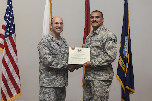 U.S. Air Force Airman 1st Class Anthony Kisiday, 17th Communications Squadron network operations technician, receives the President's Volunteer Service Award Gold medal from Col. Christopher Harris, 17th Mission Support Group Commander, at the Event Center on Goodfellow Air Force Base, Texas, June 1, 2017. The gold awards recognizes 500 or more volunteer hours to the local community. (U.S. Air Force photo by Airman 1st Class Chase Sousa/Released)
