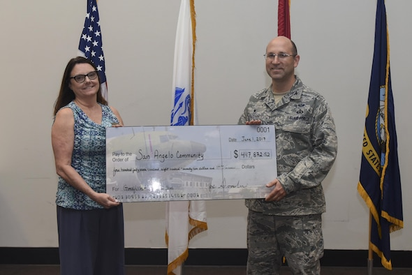 U.S. Air Force Col. Christopher Harris, 17th Mission Support Group Commander, accepts a symbolic check at the Event Center on Goodfellow Air Force Base, Texas, June 1, 2017. The check is a representation of how much the community has saved through Goodfellow volunteers. (U.S. Air Force photo by Airman 1st Class Chase Sousa/Released)
