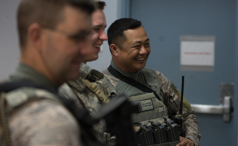 U.S. Air National Guard Staff Sgt. Melquiadez Racho, a patrol team lead with the 407th Expeditionary Security forces Squadron, shares a moment of jokes with his wingmen before shift begin May 13, 2017, in Southwest Asia. Racho is a traditional guardsman deployed from the 254th Security Forces Squadron at Andersen Air Force Base, Guam. When not on Air Force orders, Racho serves as a police instructor with the Department of Defense on Guam. He deployed with fellow ANG members. (U.S. Air Force photo by Staff Sgt. Alexander W. Riedel)