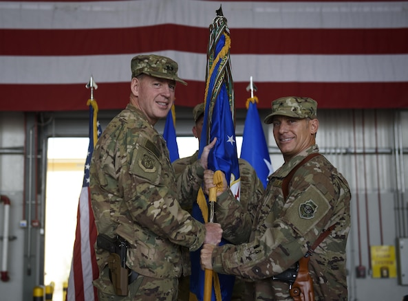 Brig. Gen. Craig Baker, the incoming 455th Air Expeditionary Wing commander, receives the 455th AEW guidon from Maj. Gen. James Hecker, the 9th Air and Space Expeditionary Task Force-Afghanistan commander, which officially grants him command of the 455th AEW during a change of command ceremony at Bagram Airfield, Afghanistan, June 3, 2017. Baker is a command pilot with more than 2,600 flying hours and has commanded at the Squadron and Wing level. (U.S. Air Force photo by Staff Sgt. Benjamin Gonsier)