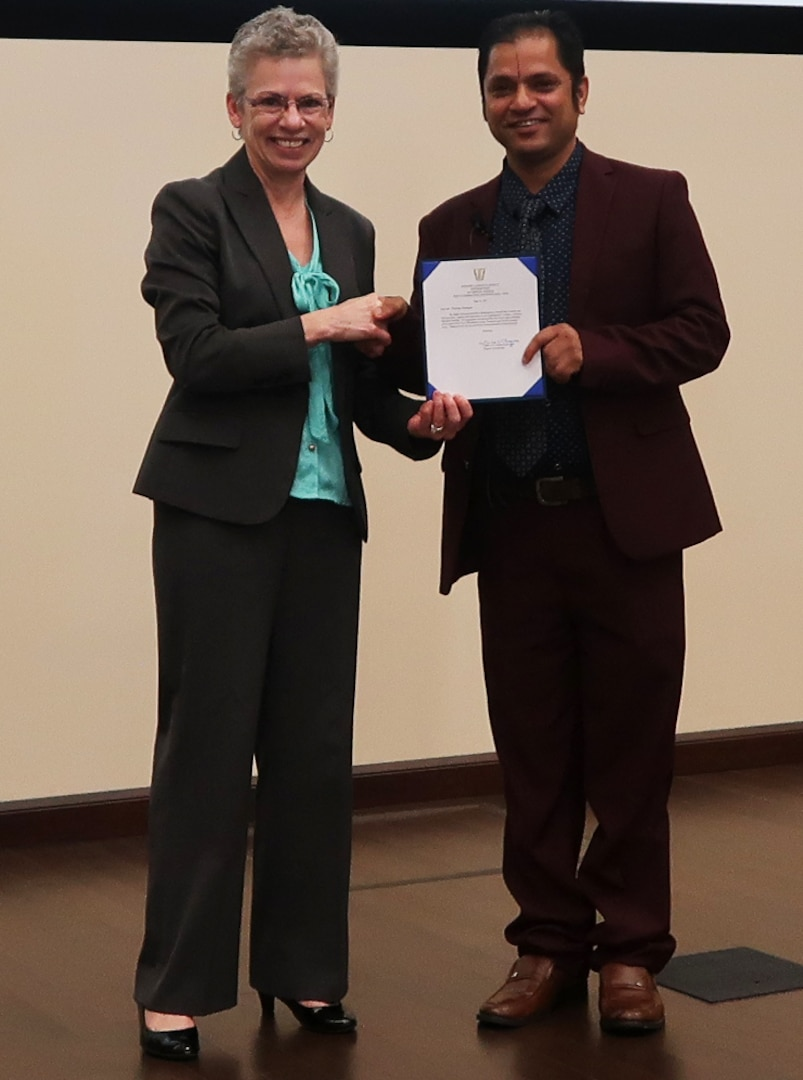 DLA Distribution deputy commander, Twila C. Gonzales, Senior Executive Service presents keynote speaker, Tika Ram Dhungana with an SES note in appreciation for his participation in DLA Distribution's Multicultural Committee Asian Americans and Pacific Islanders event held on Wednesday, May 23.