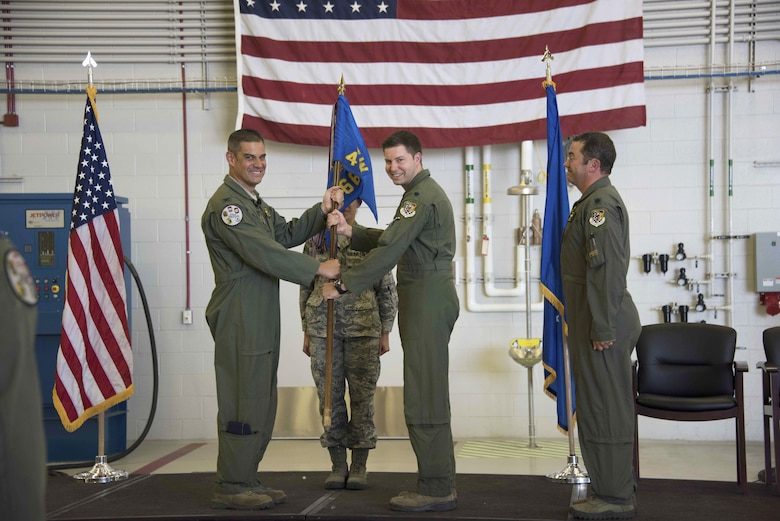 """Col. David Castaneda (left), 419th Operations Group commander, passes the 466th Fighter Squadron flag to Lt. Col. Dave DeAngelis during a change of command ceremony at Hill Air Force Base, Utah, June 4. """"We take a big step today as we move through the transition to the F-35,"""" Castaneda said. (U.S. Air Force photo/Senior Airman Justin Fuchs)"""