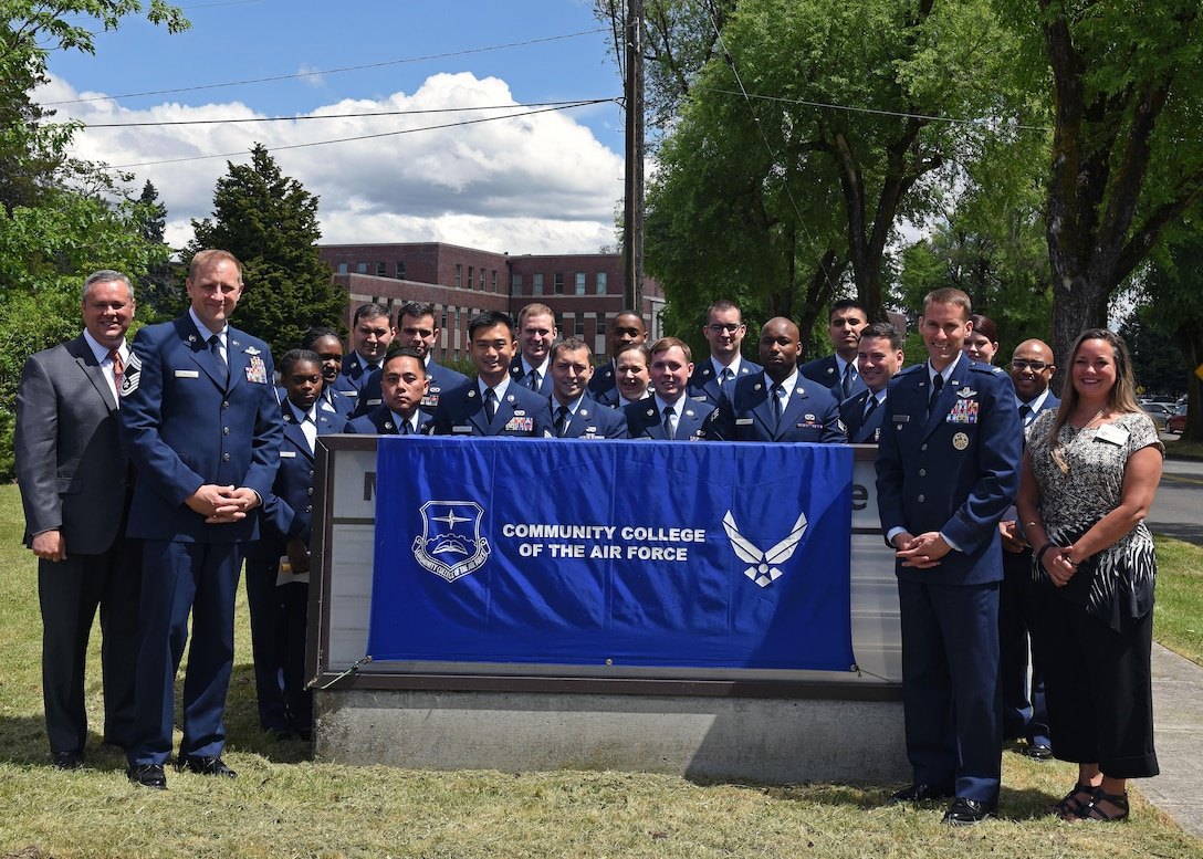 Graduates of the Community College of the Air Force stand with distinguished guests following a commencement ceremony, June 2, 2017 at the McChord Theater at Joint Base Lewis-McChord, Wash. The CCAF provides Airmen an opportunity to leverage their military training toward furthering their education. (U.S. Air Force photo/Staff Sgt. Whitney Taylor)