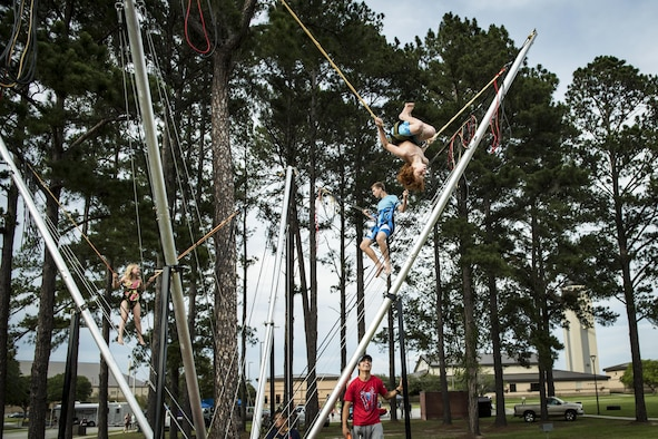 Attendees jump and flip on an attraction during the Moody Summer Block Party, June 2, 2017, at Moody Air Force Base, Ga. Members of Team Moody were encouraged to attend the event which offered a plethora of activities for all ages, including water slides, volleyball tournaments, a car show, and live entertainment. (U.S. Air Force photo by Senior Airman Janiqua P. Robinson)