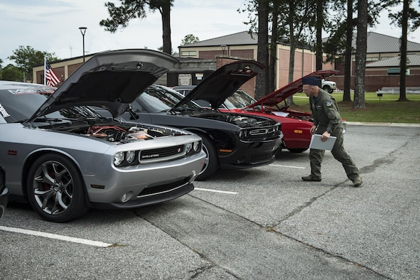 A judge looks under the hood of several cars during the car show portion of the Moody Summer Block Party, June 2, 2017, at Moody Air Force Base, Ga. Members of Team Moody were encouraged to attend the event which offered a plethora of activities for all ages, including water slides, volleyball tournaments, a car show, and live entertainment. (U.S. Air Force photo by Senior Airman Janiqua P. Robinson)