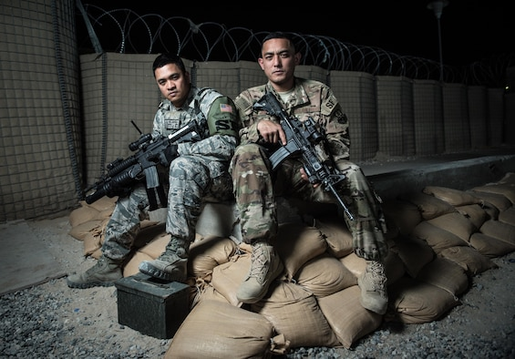 U.S. Air National Guard Staff Sgts. Neil Carranza (left) and Ricky Meno, security forces supervisors with the 407th Expeditionary Security Forces Squadron, sit for a photo May 10, 2017, at the 407th Air Expeditionary Group. The Airmen ensures only authorized personnel and vehicles enter the installation by providing vehicle search and additional overwatch via towers, cameras and other sensors at the 407th AEG. Both are traditional guardsmen with the 254th Security Forces Squadron at Andersen Air Force Base, Guam, deployed in support of Operation Inherent Resolve. (U.S. Air Force photo by Staff Sgt. Alexander W. Riedel)