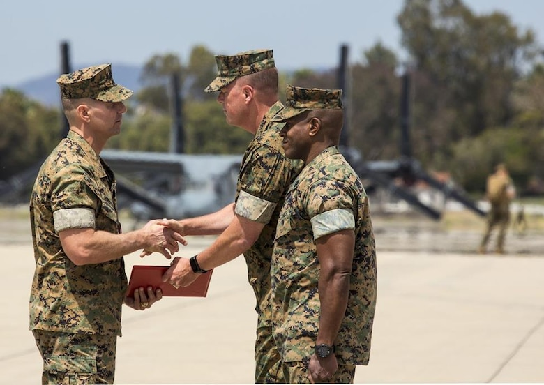 Maj. Gen. Mark Wise, middle, the 3rd Marine Aircraft Wing commanding general presents Col. Michael Borgschulte, the outgoing Marine Aircraft Group (MAG) 39 commanding officer with the legion of merit on the flightline at Marine Corps Air Station Camp Pendleton, Calif., during the MAG-39 change of command ceremony, May 25. During the ceremony, command of MAG-39 changed hands from Col. Michael Borgschulte to Col. Matthew Mowery. (U.S. Marine Corps photo by Lance Cpl. Liah Smuin/Released)