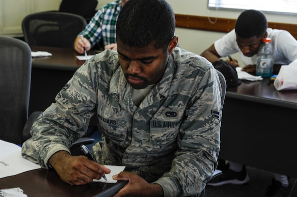 U.S. Air Force Airman 1st Class Fredrick Williams, 18th Component Maintenance Squadron electrical and environment systems apprentice, writes down a response to a question posed during Green Dot Key Influencer Training May 24, 2017 at Kadena Air Base, Japan. The Key Influencer Training provided participants with opportunities to use critical thinking to address scenarios of power-based interpersonal violence. (U.S. Air Force photo by Senior Airman Lynette M. Rolen)