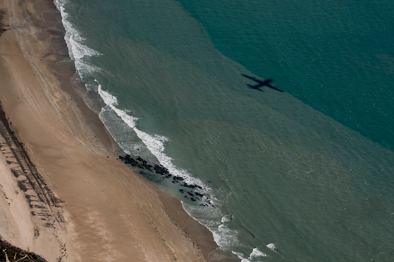 A U.S. Air Force C-130J Super Hercules assigned to the 37th Airlift Squadron at Ramstein Air Base, Germany, casts its shadow over the beaches of Normandy during a flyover in France, June 2, 2017. This event commemorates the 73rd anniversary of D-Day, the largest multinational amphibious landing and operational military airdrop in history, and highlights the U.S.' steadfast commitment to European allies and partners. Overall, approximately 400 U.S. service members from units in Europe and the U.S. are participating in ceremonial D-Day 73 events from May 31-June 7, 2017. (U.S. Air Force photo by Senior Airman Devin Boyer)