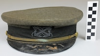 "Combination cap with green wool cover on stiff frame with hard black leather bill, gold braid chin strap, and WO1 device attached to front, with maker's mark stamp on interior lining: ""Ridabock and Company New York Trade Mark"", part of uniform used by Warrant Officer Cadmus Daniel Griffin, WWI.