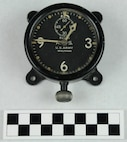 "Clock, small aviator's, made of black metal with luminous dial with white numbering, dots, and notches and with ""8 Days A.S. US Army Waltham"" with white clock hands and with hand knob at bottom and frame on back with 4 holes for mounting, with hand engraved markings on the back ""47AGV"" and ""32381"".  Made by Waltham.  Used by Coast Guard Warrant Officer Cadmus Daniel Griffin, WWI.