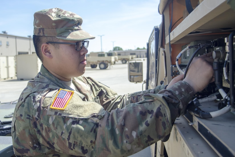Army Spc. Jesse Thepouhthay, an air traffic control equipment repairer assigned to Foxtrot Company, 6th Battalion, 101st General Support Aviation Battalion, at Fort Campbell, Ky., checks a vehicle in the motor pool, May 16, 2017. Thepouhthay's role model is his father, who immigrated to America from Laos. Army photo by Leejay Lockhart
