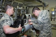 Airman 1st Class Duane Jongeling, 114th Maintenance Squadron electronic countermeasure apprentice, and Staff Sgt. Derek Jaeger, 114th Maintenance Squadron electronic countermeasure technician, perform a routine maintenance on a electronic warfare pod. These pods are the first line of defense for the 114th Fighter Wing pilots while protecting foreign and domestic airspace. (U.S. Air National Guard photo by Staff Sgt. Duane Duimstra/Released)