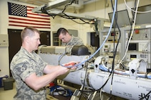Staff Sgt. Derek Jaeger, 114th Maintenance Squadron electronic countermeasure technician, and  Airman 1st Class Duane Jongeling,114th Maintenance Squadron electronic countermeasure apprentice, performs a routine maintenance on a electronic warfare pod. These pods are the first line of defense for the 175th Fighter Squadron pilots while they continue to protect foreign and domestic airspace. (U.S. Air National Guard photo by Staff Sgt. Duane Duimstra/Released)