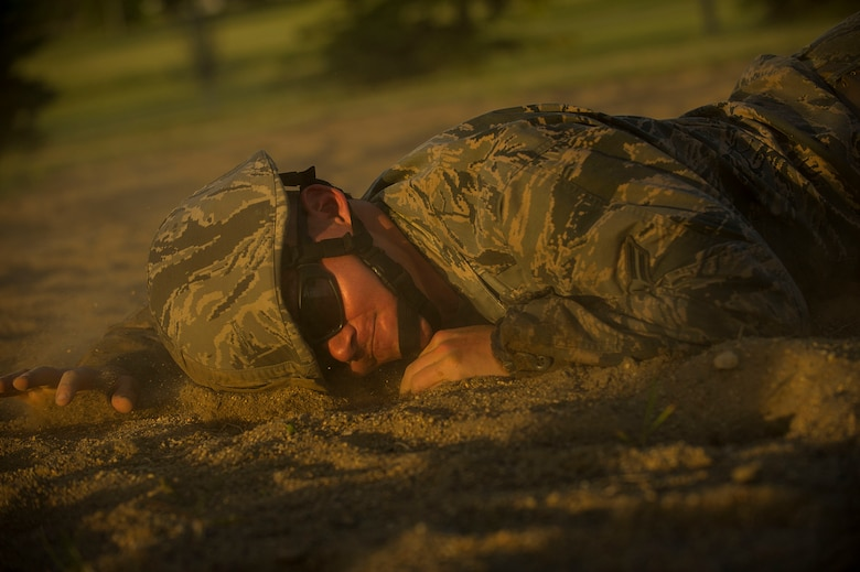 An Airman from the 5th Civil Engineer Squadron low-crawls through a sand pit during an Expeditionary Training Day at Minot Air Force Base, N.D., June 1, 2017. The day-long training event covered an array of combat operations tasks, to help prepare 5th CES Airmen for future deployments. (U.S. Air Force photo/Senior Airman Apryl Hall)