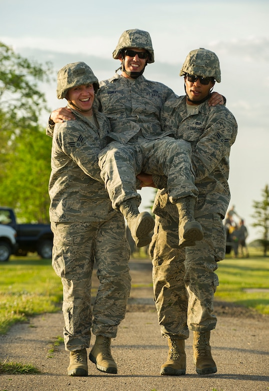"Airmen from the 5th Civil Engineer Squadron perform a ""buddy carry"" during an Expeditionary Training Day at Minot Air Force Base, N.D., June 1, 2017. During the final portion of the day-long training, Airmen completed a relay involving Self-Aid and Buddy Care techniques. (U.S. Air Force photo/Senior Airman Apryl Hall)"