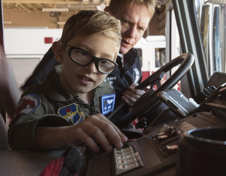 Aidan Flippo, pilot for a day candidate, pushes the siren in a fire truck May 25, 2017, at Eglin Air Force Base, Florida. Flippo, a 96th Test Wing dependent, was selected to be the 33rd Fighter Wing's pilot for a day. Aidan was born with Septo Optic Dysplasia which effects his eyes and kidneys. During his day, he met F-35 pilots, toured the aircraft, worked with aircraft maintainers and much more. (U.S. Air Force photo by Staff Sgt. Peter Thompson)