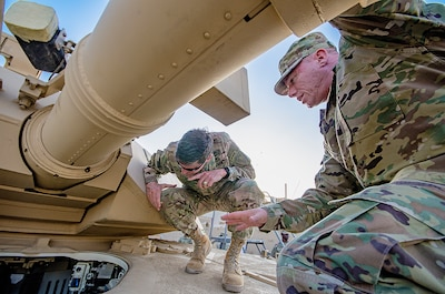 Sgt. 1st Class Frank Taylor (right), contract officer representative, Army Field Support Battalion-Kuwait explains combat enablers newly installed in an M1A2 System Enhancement Package-Version II Abrams tank to U.S. Central Command Commanding General, Army Gen. Joseph L. Votel during a tour of an Army Prepositioned Stocks-5 facility at Camp Arifjan, Kuwait, June 3. (U.S. Army photo by Justin Graff, 401st AFSB Public Affairs) (Photo Credit: Mr. Justin Graff (Rock Island Arsenal))
