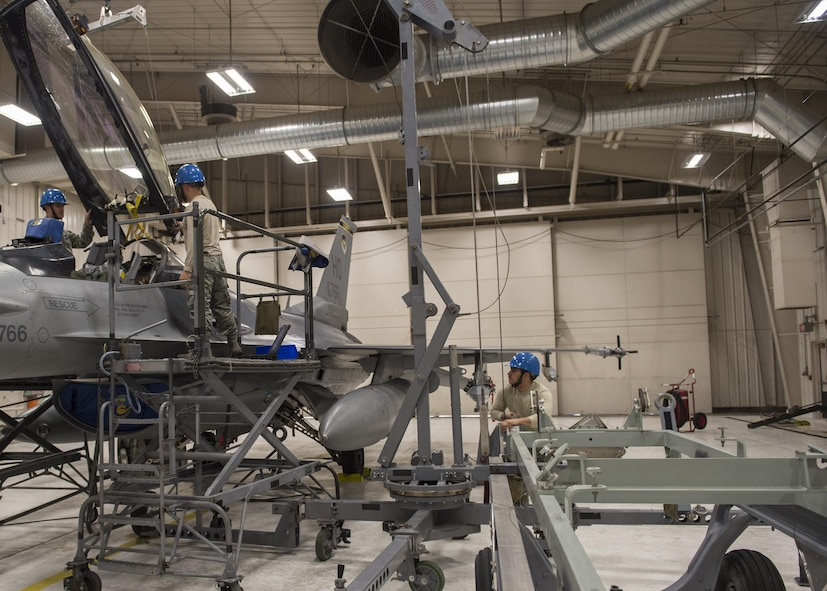 54th Maintenance Squadron egress system specialists remove a canopy from an F-16 Fighting Falcon on March 13, 2017 at Holloman Air Force Base, N.M. Egress system specialists ensure that pilots can safely eject from aircraft in the event of an emergency. They perform scheduled and unscheduled maintenance on seats, hatches, canopies and modules. (U.S. Air Force photo by Senior Airman Emily Kenney)