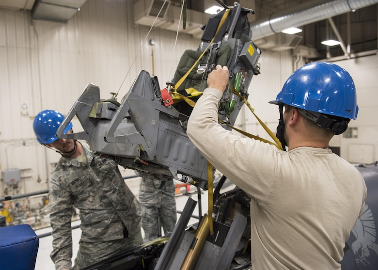 Tech. Sgt. Kevin Mayo (left), the 54th Maintenance Squadron egress section assistant Non-Commissioned Officer in Charge, and Staff Sgt. Mitchell Lawhorn (right), a 54th Maintenance Squadron egress systems Craftsman, remove an ejection seat from an F-16 Fighting Falcon on March 13, 2017 at Holloman Air Force Base, N.M. Egress system specialists ensure that pilots can safely eject from aircraft in the event of an emergency. They perform scheduled and unscheduled maintenance on seats, hatches, canopies and modules to ensure pilots can safely eject if necessary. (U.S. Air Force photo by Senior Airman Emily Kenney)