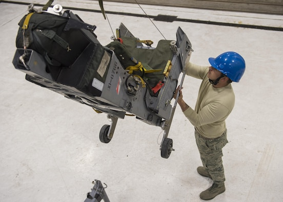 Airman 1st Class Steven Phelps, a 54th Maintenance Squadron egress systems journeyman, removes the ejection seat of an F-16 Fighting Falcon on March 13, 2017 at Holloman Air Force Base, N.M. Egress specialists work hand-in-hand with Aircrew Flight Equipment to ensure pilots have the necessary equipment in case of an emergency. (U.S. Air Force photo by Senior Airman Emily Kenney)