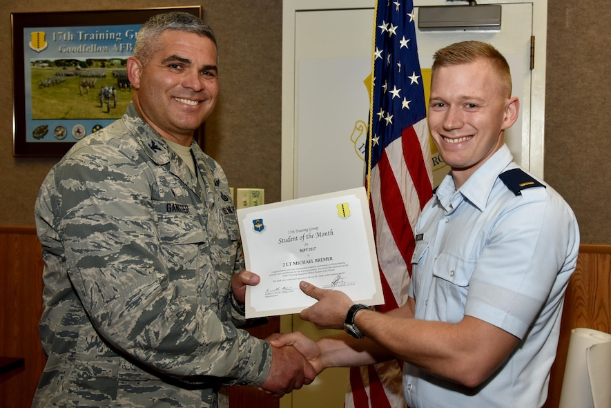 U.S. Air Force Col. Alex Ganster, 17th Training Group Commander, presents the 315th Training Squadron Officer Student of the Month award for May 2017 to 2nd Lt. Michael Bremer, 315th TRS student, in Brandenburg Hall on Goodfellow Air Force Base, Texas, June 2, 2017. (U.S. Air Force photo by Staff Sgt. Joshua Edwards/Released)