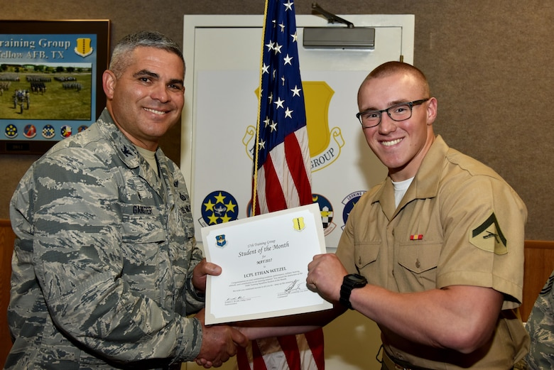 U.S. Air Force Col. Alex Ganster, 17th Training Group commander, presents the 316th Training Squadron Student of the Month award for May 2017 to Lance Cpl. Ethan Wetzel, 316th TRS student, in Brandenburg Hall on Goodfellow Air Force Base, Texas, June 2, 2017. (U.S. Air Force photo by Staff Sgt. Joshua Edwards/Released)
