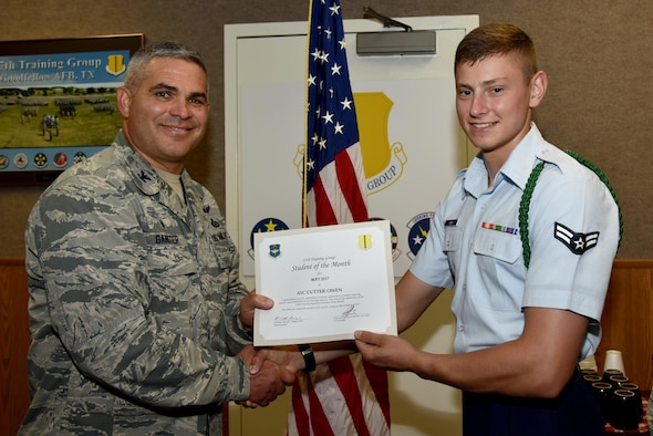 U.S. Air Force Col. Alex Ganster, 17th Training Group Commander, presents the 312th Training Squadron Student of the Month award for May 2017 to Airman 1st Class Cutter Owen, 312th TRS student, in Brandenburg Hall on Goodfellow Air Force Base, Texas, June 2, 2017. (U.S. Air Force photo by Staff Sgt. Joshua Edwards/Released)