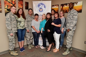 Airmen and Family Readiness Center members gather for a photo at Schriever Air Force Base, Colorado, Friday, June 2, 2017. The A&FRC is there to help base members and their families to overcome challenges by providing a variety of tools and resources. (U.S. Air Force photo/Senior Airman Arielle Vasquez)