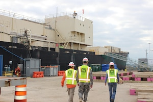 Program Manager Hans Honerlah, Baltimore District's Radiological Health Physics Regional Center of Expertise; Baltimore District Commander Col. Ed. Chamberlayne; and Baltimore District Project Manager Brenda Barber, project manager for the ongoing STURGIS decommissioning and dismantling work in Galveston, walk on the pier alongside the vessel during a site visit on Dec. 8, 2015.