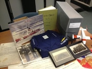 Mixed donation to the Coast Guard Heritage Asset Collection and Archives including uniform, scrapbook, photographs, documents, logbooks, etc.  Coast Guard Museum, Academy, New London, CT.