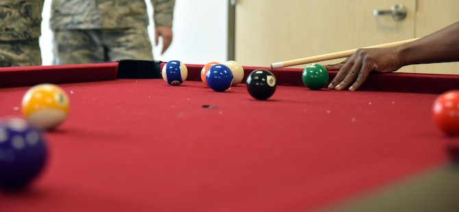 An Airman lines up a shot while playing pool during the Schriever event center opening celebration at Schriever Air Force Base, Colorado, Friday, June 2, 2017. The facility featured many games for Airmen to enjoy, such as darts and table tennis. (U.S. Air Force photo/Airman 1st Class William Tracy)