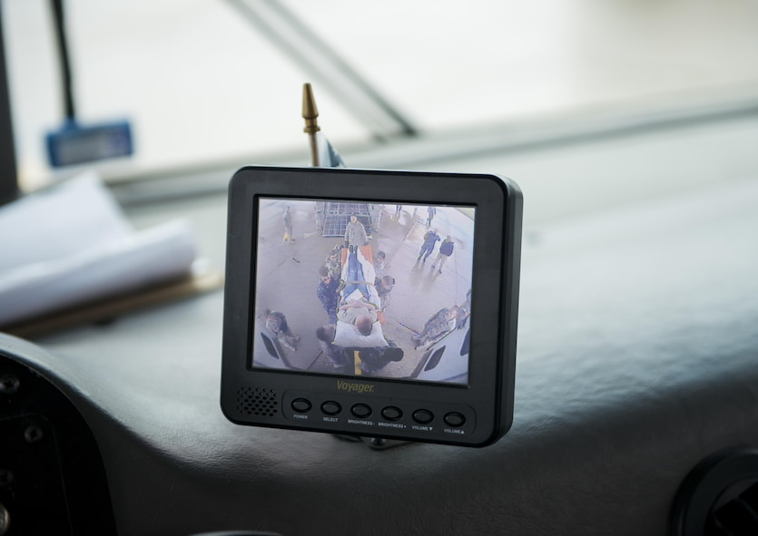 "A backup camera on a military vehicle captures a ""patient"" being transferred by medical personnel from bus to C-130 aircraft as part of a joint service training exercise involving members from the 914th Aeromedical Staging Squadron and medical personnel from other branches of the military. Participants carry out simulated emergency scenarios to gain skills and experience that can be applied to real world situations. (U.S. Air Force photo by Tech. Sgt. Stephanie Sawyer)"