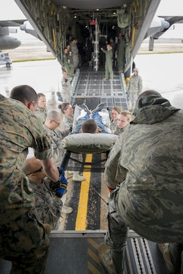"Members of the 914th Aeromedical Staging Squadron, along with other medical personnel from different branches of service, transfer a ""patient"" from bus to C-130 Aircraft as part of a joint service training exercise. Participants carry out simulated emergency scenarios to gain skills and experience that can be applied to real world situations. (U.S. Air Force photo by Tech. Sgt. Stephanie Sawyer)"