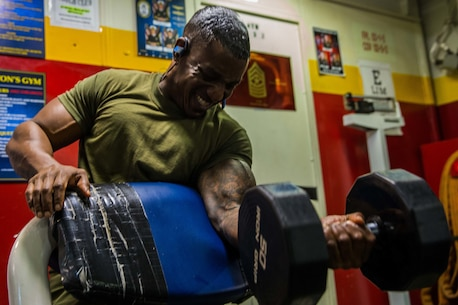 USS MAKIN ISLAND, Gulf of Aden (Feb. 8, 2017) U.S. Marine Gunnery Sgt. Julian Fyffe does arm curls during physical training aboard the USS Makin Island (LHD8), Feb. 8. The Makin Island has a sizeable gym complete with free-weights, weight training machines and cardio equipment. Fyffe is with Charlie Co., Battalion Landing Team 1st Bn., 4th Marines, 11th Marine Expeditionary Unit. (U.S. Marine Corps photo by Lance Cpl. Brandon Maldonado)