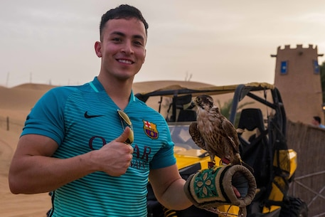 United Arab Emirates (March 19, 2017) U.S. Marine Cpl. Jesus Oliveros, a legal clerk with the 11th Marine Expeditionary Unit (MEU), poses for a picture while holding a falcon as part of a Sunset Safari tour during the 11th MEU's port visit to United Arab Emirates, March 19. Port calls are a unique experience for Marines because they provide an opportunity for Marines to immerse themselves with a different culture while on deployment. The Makin Island Amphibious Ready Group/11th MEU is currently deployed to the U.S. 5th Fleet area of operations in support of regional security and stability. (U.S. Marine Corps by Lance Cpl. Brandon Maldonado)