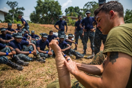 WELISARA NAVAL BASE, Sri Lanka (March 29, 2017) U.S. Navy Petty Officer 3rd Class Ryan Walker, a hospital corpsman with Battalion Landing Team 1st Bn., 4th Marines, 11th Marine Expeditionary Unit (MEU), shows Sri Lankan Marines the proper way to apply a dressing to a wound during the tactical casualty combat care portion of a military tactics training and exchange at Welissara Naval Base as part of a theater security cooperation engagement, March 29. Over the course of the engagement, Marines with the 11th MEU, alongside Marines and Sailors with the Sri Lankan Navy will take part in basic military tactics exercises, humanitarian assistance and disaster relief training, and community relations projects. (U.S. Marine Corps photo by Cpl. Devan K. Gowans)