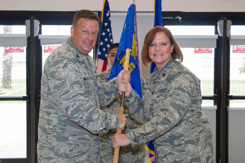 Col. Matthew Wallace, 45th Mission Support Group commander, presents Maj. Dawn Baker, 45th Logistics Readiness Squadron commander, with a guidon during a change of command ceremony June 6, 2017, at Patrick Air Force Base, Fla. Changes of command are a military tradition representing the transfer of responsibilities from the presiding official to the upcoming official.